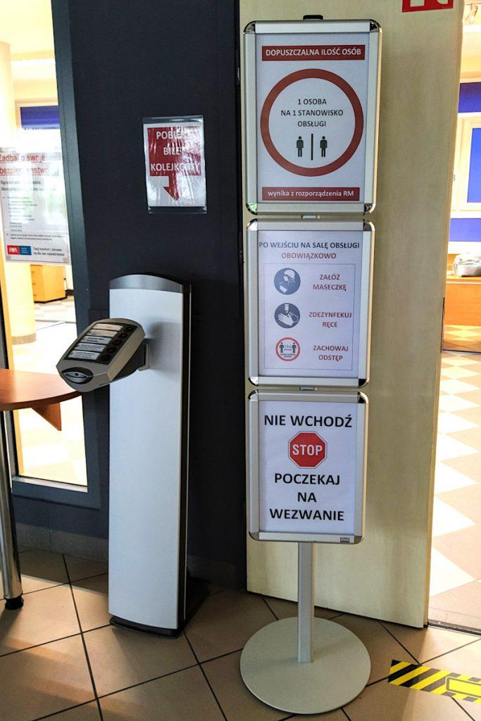 Znaki informujące o zasadach bezpieczeństwa - 1 osoba na 1 stanowisku obsługi, obowiązkowe maseczki, dezynfekcja rąk oraz odstęp oraz konieczność oczekiwania na wezwanie