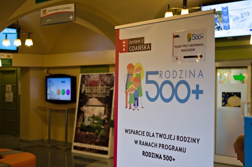 """Na zdjęciu widoczny jest rollup z logotypem Jestem z Gdańska, logotypem programu 500+ oraz napisem """"Wsparcie dla Twojej rodziny w ramach programu Rodzina 500+"""". W tle korytarz budynku biurowego."""