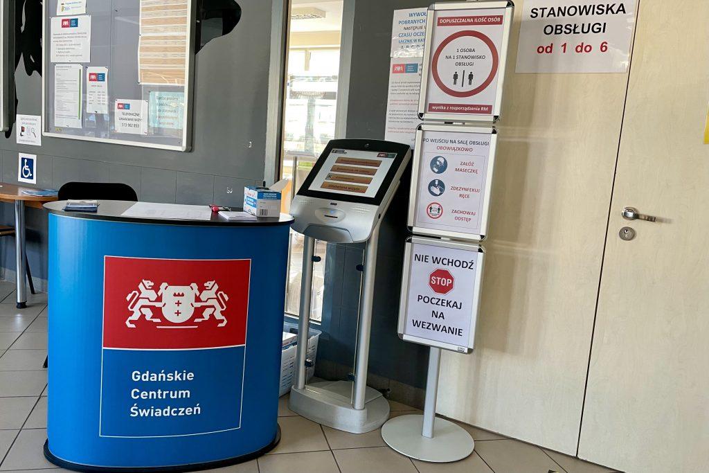 Na zdjęciu znajduje się stanowisko dla pracownika, automat biletowy oraz oznakowanie przypominające o konieczności założenia maseczki, dezynfekcji rąk oraz zachowania bezpiecznego dystansu.